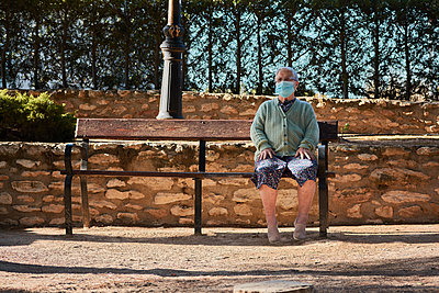 Older woman sitting on a park bench with her mask on - p1166m2218060 by Cavan Images