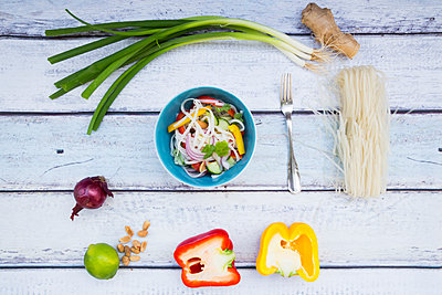 Bowl of glass noodle salad with vegetables and ingredients on wood - p300m1192165 by Larissa Veronesi