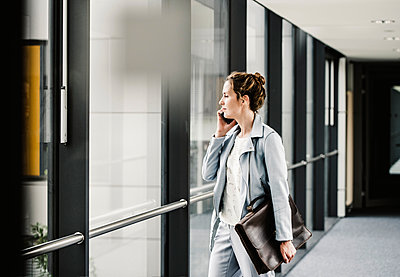 Businesswoman on cell phone looking out of window in office passageway - p300m2024115 von Uwe Umstätter