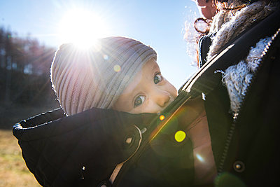 Sunlit close up of baby boy wearing knit hat, carried in baby sling by mother - p429m1226798 by Bonfanti Diego