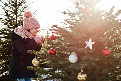 Girl looking at baubles on forest christmas tree - p429m1557603 by Gpointstudio