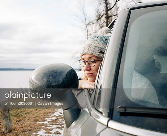 portrait of blonde woman with glasses looking out of car window water - p1166m2090661 by Cavan Images