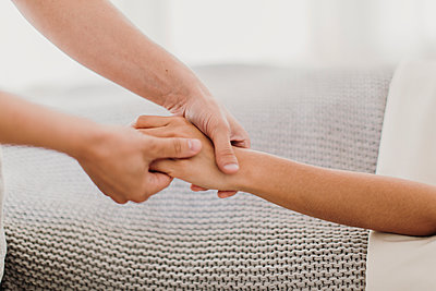 A woman receives a hand massage from a professional massage therapist - p1166m2107017 by Cavan Images