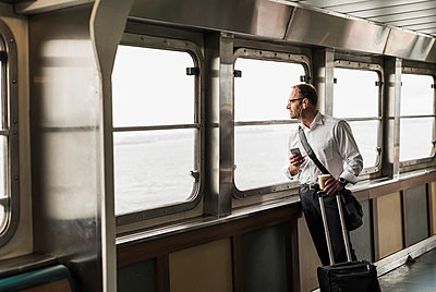 Businessman on a ferry looking out of window - p300m2013074 by Uwe Umstätter