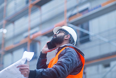Construction engineer on the phone at construction site - p300m2160289 von Sigrid Gombert