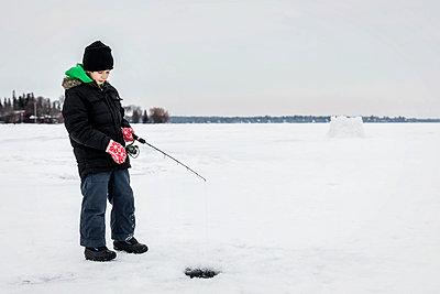 Boy patiently waiting for a bite while ice fishing at Wabamun Lake; Wabamun, Alberta, Canada - p442m2074053 by LJM Photo