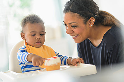 Mixed race mother giving baby son cupcake in high chair - p555m1412283 by JGI/Tom Grill