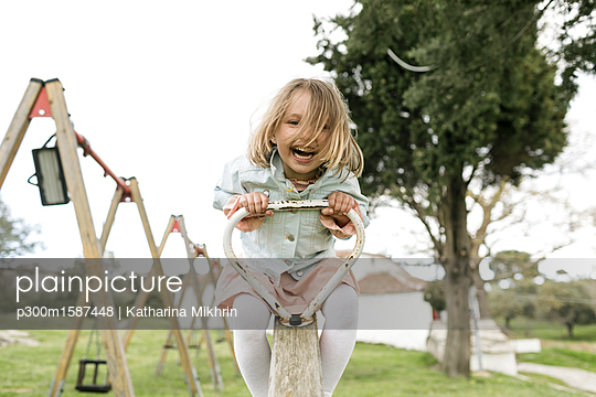 Excited little girl having fun on a seesaw