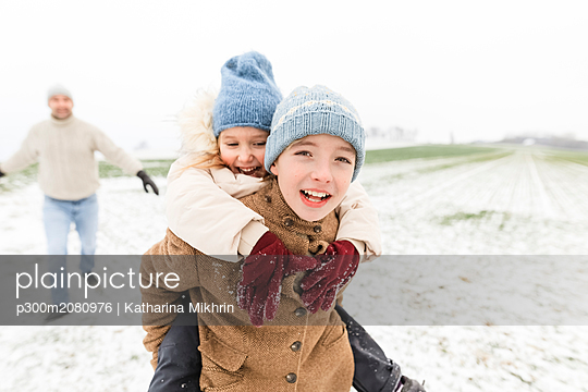 Boy carrying happy sister piggyback in winter landscape - p300m2080976 by Katharina Mikhrin