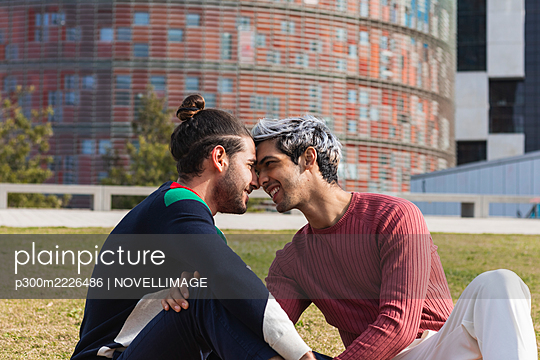 Smiling affectionate man looking at male partner while sitting in park - p300m2226486 by NOVELLIMAGE