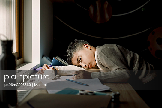 Tired pre-adolescent boy resting head on table in bedroom - p426m2296369 by Maskot