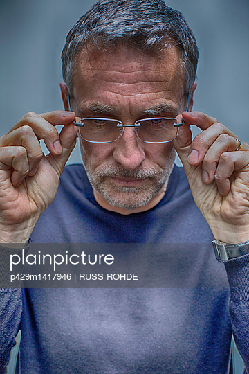 Portrait of greying mature man removing glasses - p429m1417946 by RUSS ROHDE