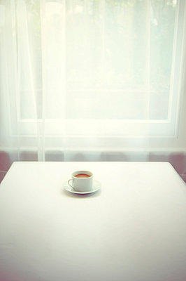 Single coffee cup on table by window - p1072m829368 by Neville Mountford-Hoare