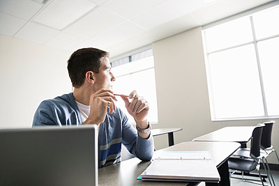 Male student looking out window in college classrom - p1192m1044085f by Hero Images