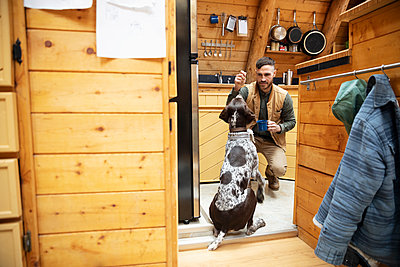 Man giving dog a treat in cabin kitchen - p1192m2093902 by Hero Images