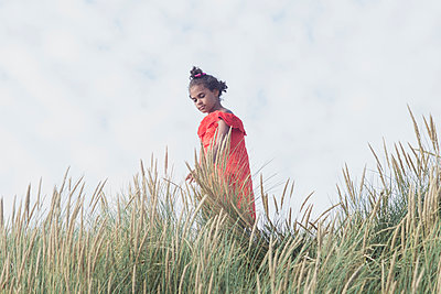 Girl standing in the dunes - p1323m2015155 von Sarah Toure