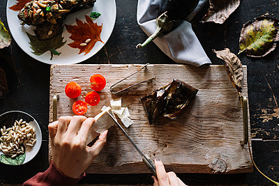 Woman slicing cheese on rustic chopping board, overhead view of hands - p429m2052366 by Alberto Bogo