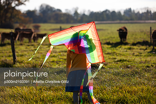 Rear view of girl in field with kite - p300m2103391 by Anette Christina Götz