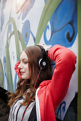 Portrait of teenage girl wearing headphones at a painted train car - p300m2104234 von Roger Richter