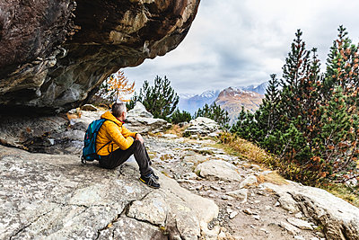 Hiker sitting and looking over alpine plateau in autumn, Sondrio, Italy - p300m2144477 by 27exp