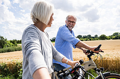 Man talking to woman while walking with bicycle on sunny day - p300m2293842 by Uwe Umstätter