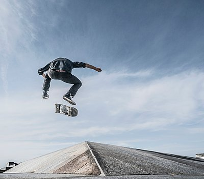 Young man skateboarding on roof - p429m1135573 by JLPH
