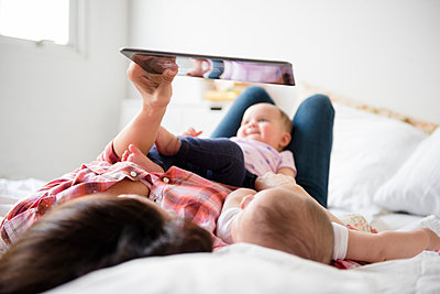 Caucasian mother on bed with twin baby daughters using digital tablet - p555m1301839 by JGI/Jamie Grill