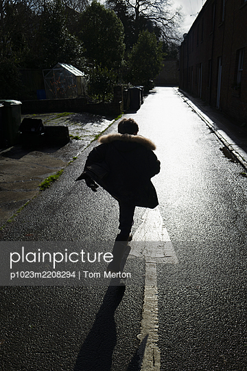 Boy running on sunny wet street - p1023m2208294 by Tom Merton