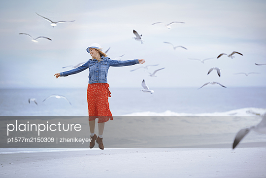 Woman jumping next to the ocean surrounded by flying seagulls - p1577m2150309 by zhenikeyev