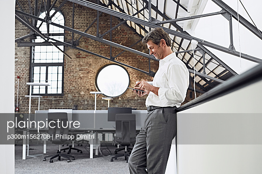 Mature businessman using smartphone in modern office - p300m1562708 by Philipp Dimitri