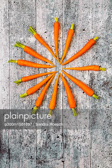 Baby carrots on wood - p300m1581697 von Sandra Roesch
