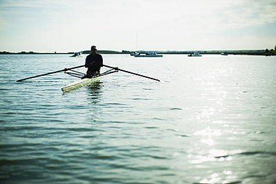 A middle-aged man in a rowing boat on the water.  - p1100m876296f by Jamie Kripke