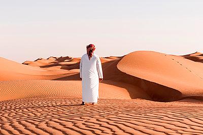 Bedouin in National dress standing in the desert, rear view, Wahiba Sands, Oman - p300m2104070 by Valentin Weinhäupl