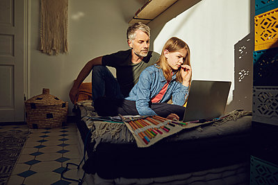 Father helping daughter doing homework and using laptop - p300m2189316 by Maya Claussen