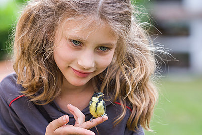 Portrait of smiling girl with great titmouse  sitting on her finger - p300m919834 by Andreas Pacek