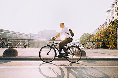 Full length of businessman riding bicycle on street in city against sky - p426m2169398 by Maskot