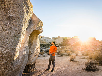 Male boulderer looking up at boulder in Joshua Tree National Park at dusk, California, USA - p429m1447800 by Manuel Sulzer