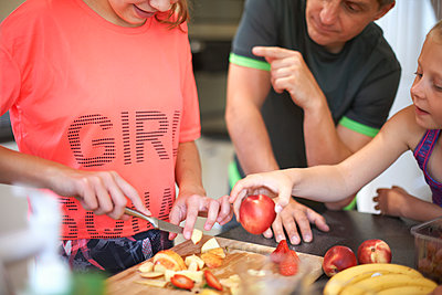 Cropped shot of teenage girl and family chopping fresh fruit  in kitchen - p429m1494689 by Peter Muller