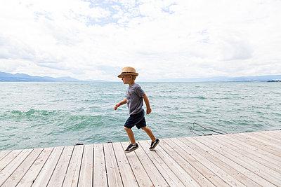 Boy with hat running on boardwalk - p756m1464813 by Bénédicte Lassalle