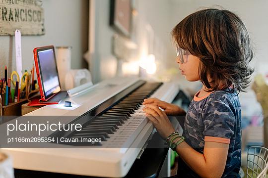 Kid playing on a white smart piano keyword while look at  iPad - p1166m2095854 by Cavan Images