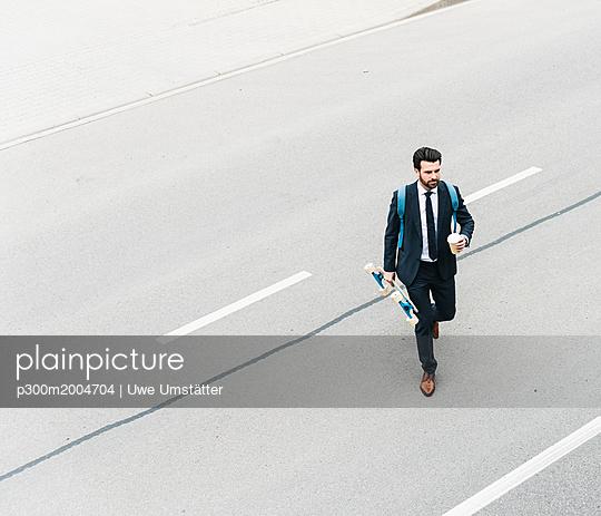 Businessman with takeaway coffee and skateboard walking on the street - p300m2004704 von Uwe Umstätter