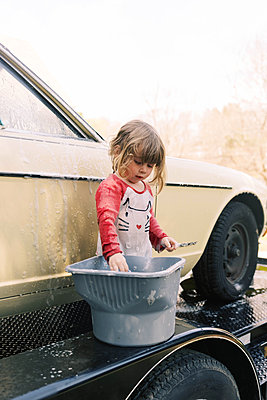 Toddler girl washing a classic car. - p1166m2190677 by Cavan Images