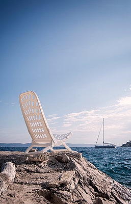 Chair by the sea - p1443m2039245 by SIMON SPITZNAGEL