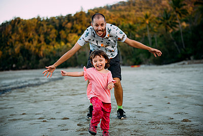 Australia, Queensland, Mackay, Cape Hillsborough National Park, happy father running after his daughter at the beach - p300m2058824 by Gemma Ferrando