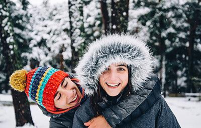 Portrait of happy young couple in winter forest - p300m2144578 von Oscar Carrascosa Martinez
