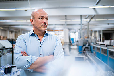Portrait of a serious businessman in a factory - p300m2170631 by Daniel Ingold