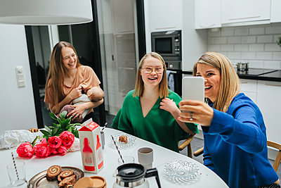 Family at table taking selfie - p312m2080503 by Anna Roström