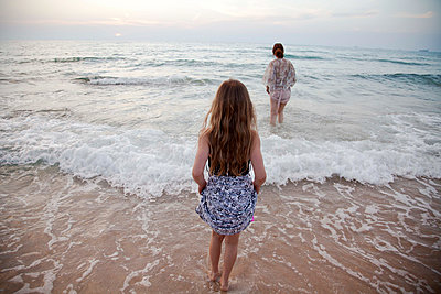 Mother and daughter walking in waves on beach - p555m1408867 by Shestock