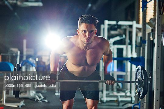 Man lifting barbell in gym - p300m1581488 von gpointstudio
