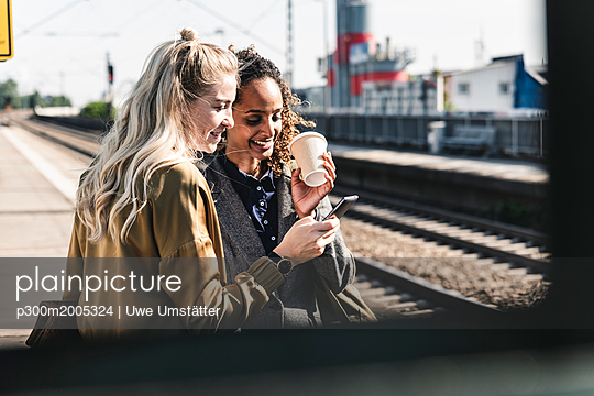 Friends waiting at train station looking at smartphone - p300m2005324 von Uwe Umstätter